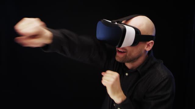 vídeos y material grabado en eventos de stock de hombre con gafas de realidad virtual. enemigo imaginario de perforación - golpear