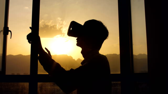 vídeos de stock, filmes e b-roll de homem que usa auriculares da realidade virtual no por do sol - jogador de videogame