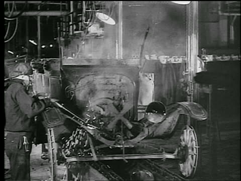 b/w 1930 man using welding torch on car to take it apart for scrap metal / newsreel - 1930 stock videos & royalty-free footage