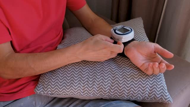 vídeos de stock, filmes e b-roll de homem usando dispositivo de pressão de pulso - almofada