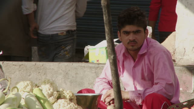 man vendor in pink shirt sitting by cauliflower - gourd stock videos & royalty-free footage