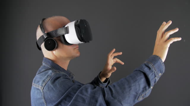 Man viewing through VR headset and moving his hands