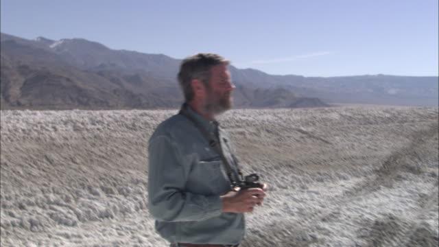 a man views the sierra nevada mountains with binoculars. - binoculars stock videos & royalty-free footage