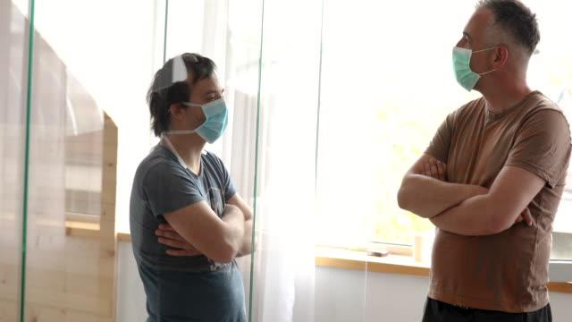 uomo in visita al fratello in quarantena mentre segue la regola di due metri l'uno dall'altro - divisione video stock e b–roll
