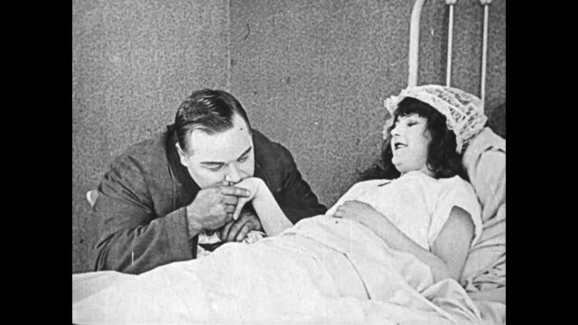 1919 Man (Fatty Arbuckle) visits a sleeping woman in a clinic, they are happy to see each other, he kisses her hand, and then cleans an apple before biting into it