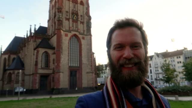 vidéos et rushes de vlogging homme en face de l'église - vidéo de stock - devant