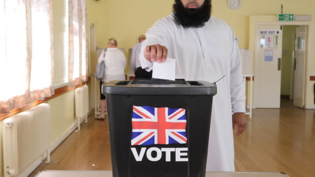 4k: man voting at ballot box at the uk election - voting at polling station - voting ballot stock videos and b-roll footage