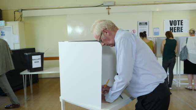 4k dolly: man voting at booth at polling place. elections - voting ballot stock videos and b-roll footage