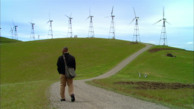 ws man w/ laptop bag walking on gravel road toward wind turbines on hillside / livermore, california, usa - laptop bag stock videos and b-roll footage