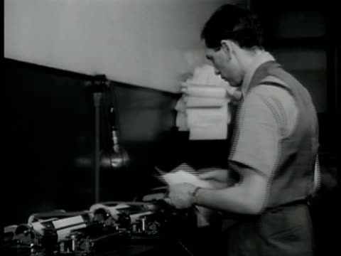 man w/ pipe handing out papers man standing row of teletypes pulling paper out cu newspaper clippings editor names 'george axelson raymond daniell... - ニューヨークタイムズ点の映像素材/bロール