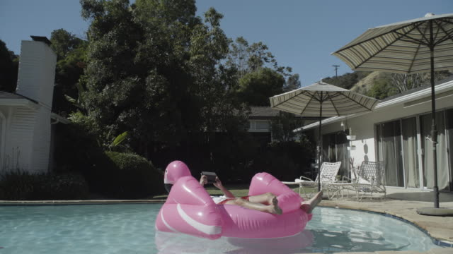 ws man w/ tablet in pool on pink inflatable - pink shirt stock videos and b-roll footage
