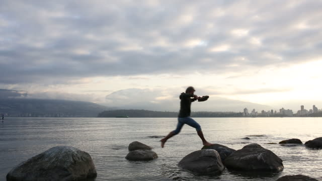 man wades in shallows, then looks out to city from tidal rocks - barfuß stock-videos und b-roll-filmmaterial