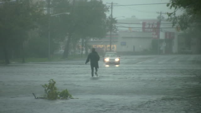 vídeos de stock, filmes e b-roll de a man wades through fast moving flood waters as hurricane irene batters the town of island park ny a vehicle decides not to chance it and turns... - vadear