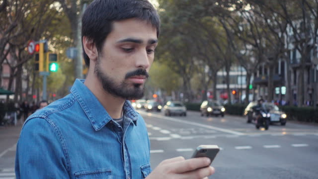 vidéos et rushes de 4k | man waiting for a car service in a big city of europe. he is standing on the street checking the smartphone and looking around. he wears blue denim shirt and has short dark hair and hipster beard - audio disponible en ligne