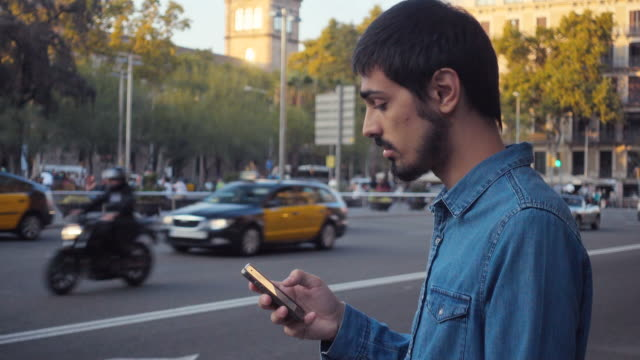 4K | Man waiting for a car service in a big city of Europe. He is standing on the street checking the smartphone and looking around. He wears blue denim shirt and has short dark hair and hipster beard