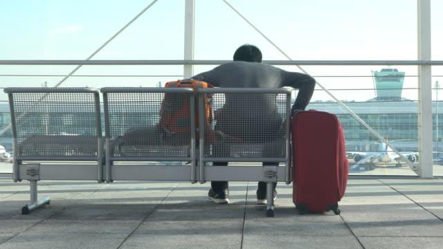 vídeos de stock, filmes e b-roll de homem à espera de um avião no aeroporto - pacote arranjo