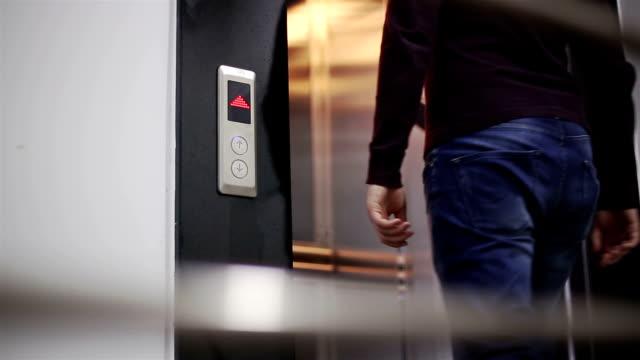 Hombre espera delante de un ascensor