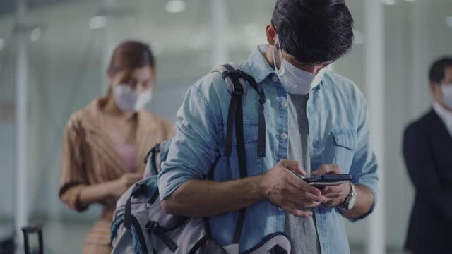 vídeos y material grabado en eventos de stock de hombre esperando en la cola en el aeropuerto usar máscara facial - rucksack