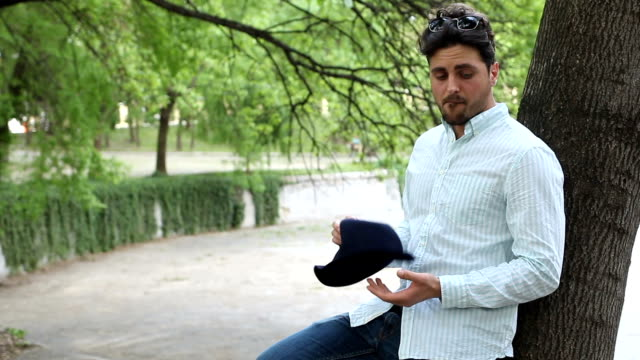 Man waiting in the park and looking at his phone