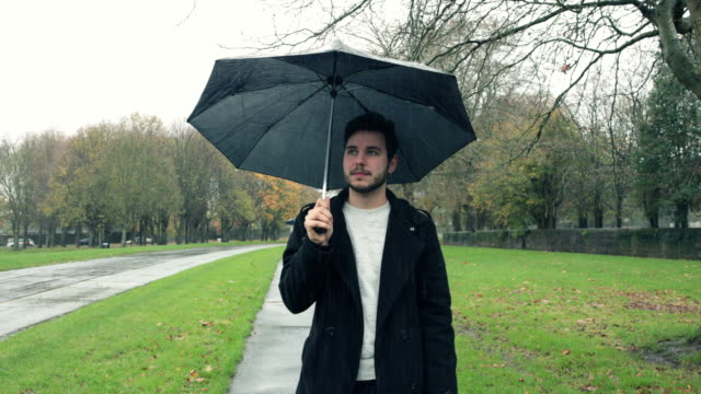 man waiting in the rain with an umbrella - waiting stock videos & royalty-free footage