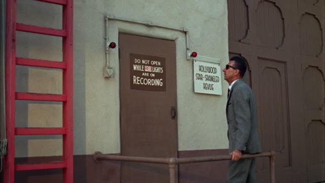 ms man waiting outside of sound stage door of warner bros studio - warner bros. stock videos & royalty-free footage