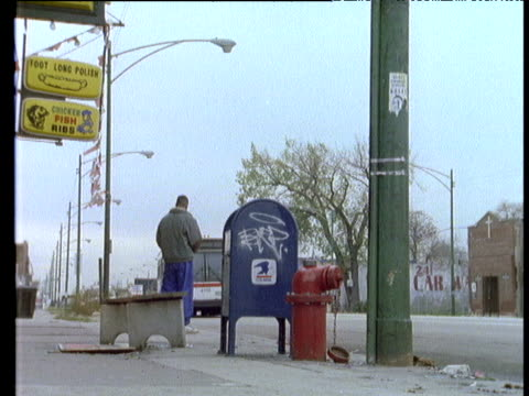 man waits at bus stop beside graffiti covered post box and red fire hydrant flags bus gets on bus exits shot. - mailbox stock videos and b-roll footage