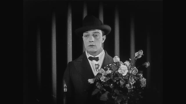 1920 man (buster keaton) waits for his arriving guest at the wrong track in grand central station - bouquet stock videos & royalty-free footage