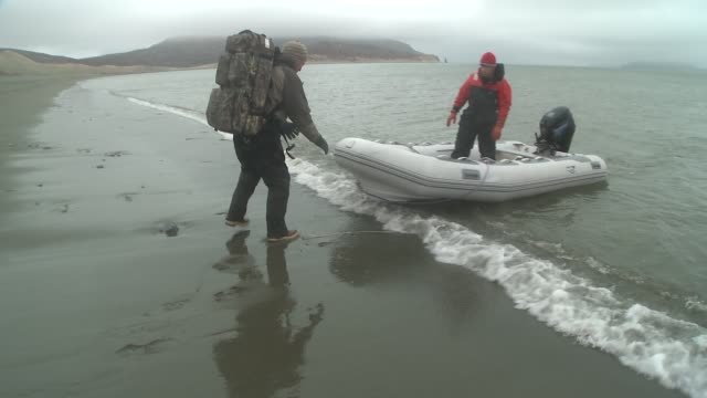 a man waits on a wet, cold beach for another man in a pontoon boat to come ashore with equipment. - wet wet wet stock videos & royalty-free footage
