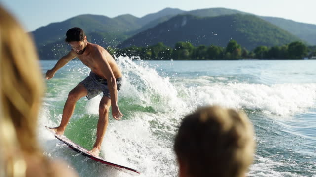 man wake surfing on alpine lake at sunset - nackter oberkörper stock-videos und b-roll-filmmaterial