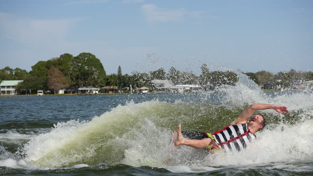 a man wake surfing wakeboarding behind a boat on a lake and doing a trick then wipeout. - slow motion - surf stock videos & royalty-free footage