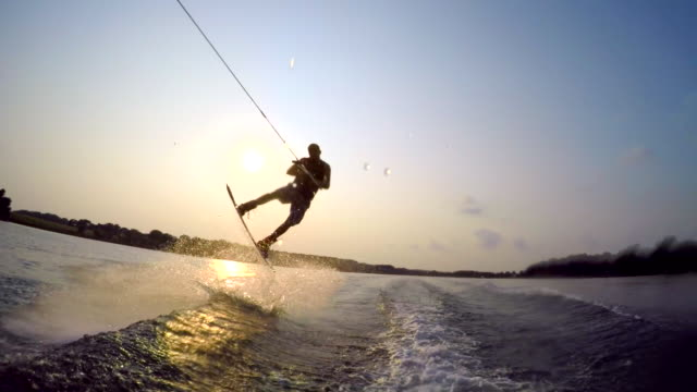 a man wakeboarding behind a boat. - slow motion - 人工物点の映像素材/bロール