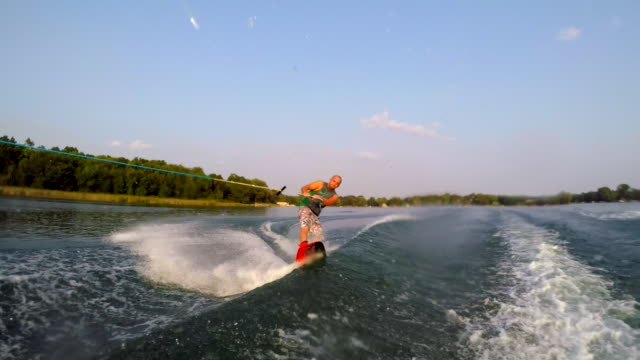 a man wakeboarding behind a boat. - slow motion - wakeboarding stock videos & royalty-free footage