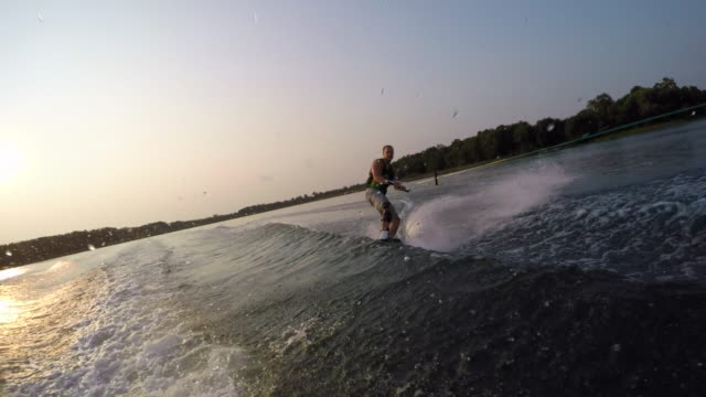 a man wakeboarding behind a boat. - slow motion - waterskiing stock videos & royalty-free footage