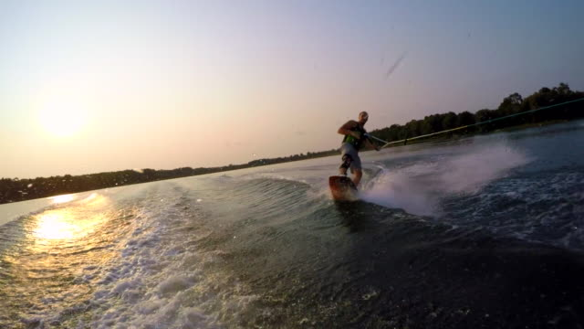 A man wakeboarding behind a boat. - Slow Motion