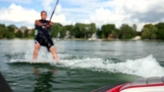 a man wakeboarding behind a boat. - slow motion - ウェイクボーディング点の映像素材/bロール