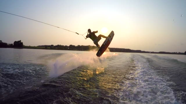 a man wakeboarding behind a boat. - wakeboarding stock videos and b-roll footage
