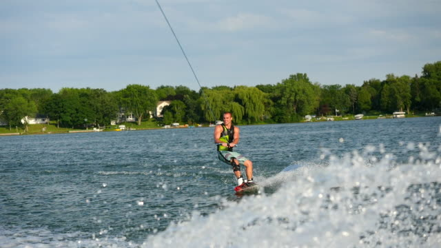 a man wakeboarding behind a boat. - ウェイクボーディング点の映像素材/bロール