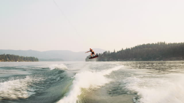 man wakeboarding behind a ski boat - rope stock videos & royalty-free footage