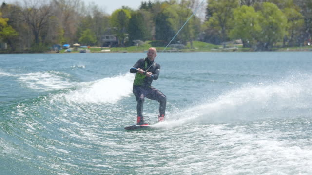 a man wakeboards behind a boat while wearing a wetsuit. - slow motion - waterskiing stock videos & royalty-free footage