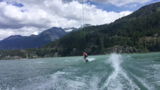 man wakeboards behind motorboat, on mountain lake - boat point of view stock videos & royalty-free footage