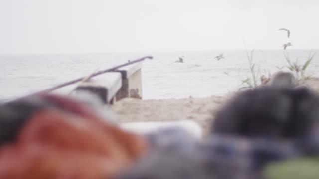 man wakes up in sleeping bag on beach, slow motion - 寝袋点の映像素材/bロール