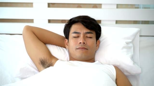 男は目を覚ます、彼の目を開く - ヘッドボード点の映像素材/bロール