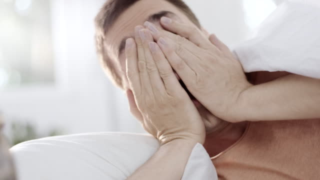 Mann aufwachen und Wecker ausschalten