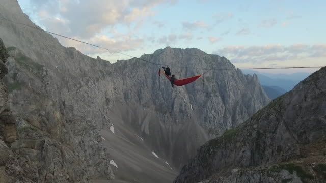 man waking up in a hammock on a highline