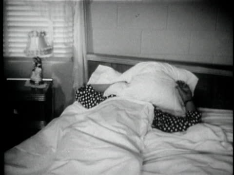 b/w ms man waking up in bed, looking out window, and putting pillow over his face / usa - pillow stock videos and b-roll footage