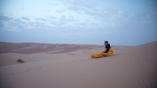 man waking up in sleeping bag in desert - 寝袋点の映像素材/bロール
