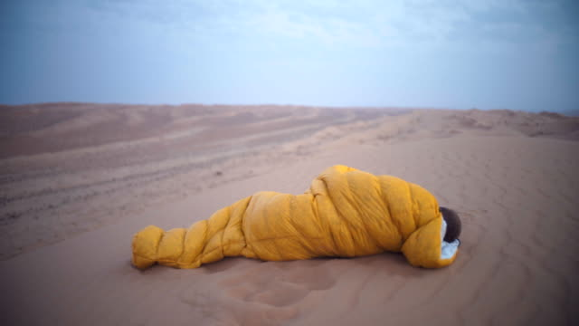 Man waking up in sleeping bag in desert