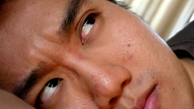 man waking up on bed with eyes looking around - close up shot