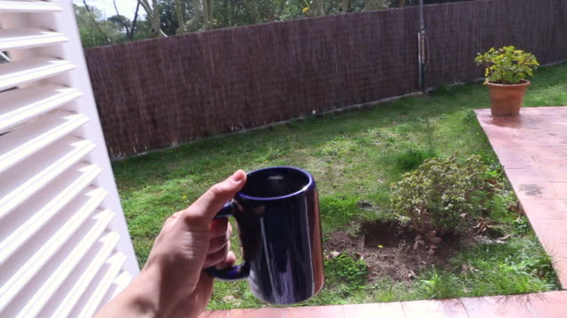 Man waking up on morning at home preparing a coffee on a large cup and going to the backyard from personal point of view on a sunny and warm day.
