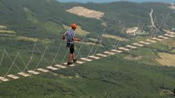 Man Walking a Dangerous Suspension Bridge